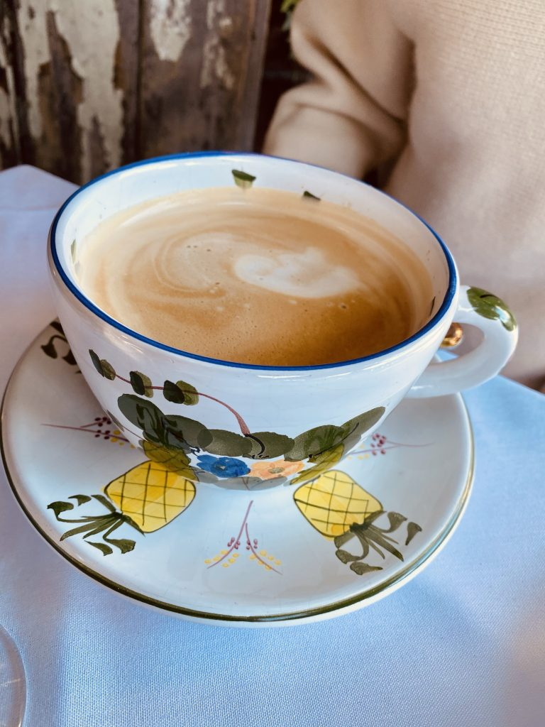 creamy latte in hand painted china, pineapple plates