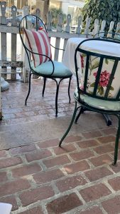 Alfresco dining, shabby chic chairs, white wooden fence