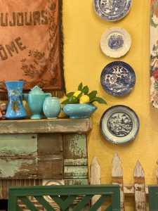 Fireplace mantle with patina, picket fence indoors, blue and white china on yellow wall