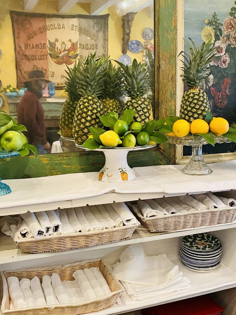 Fresh fruit displays, pineapple, citrus, french flag, mirror with patina
