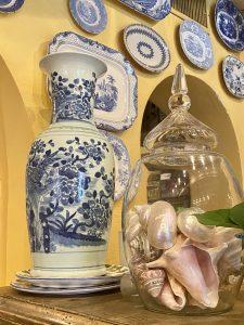 blue and white china hung on yellow walls, seashells