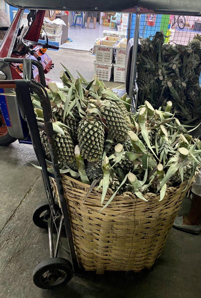 Fresh cut pineapples, baskets of pineapples, Bangkok produce market, Pak Khlong Talat, tuk tuk filled with pineapples